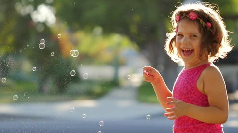 Happy girl having fun blowing soap bubbles into father's face outdoors. Slow motion.