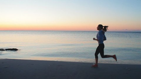 young woman with a slender figure is engaged in gymnastics at sea at sunrise. She makes a run along the sea coast. steadicam shot
