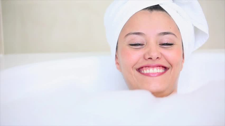 Beauty woman playing with bubbles while taking a bath