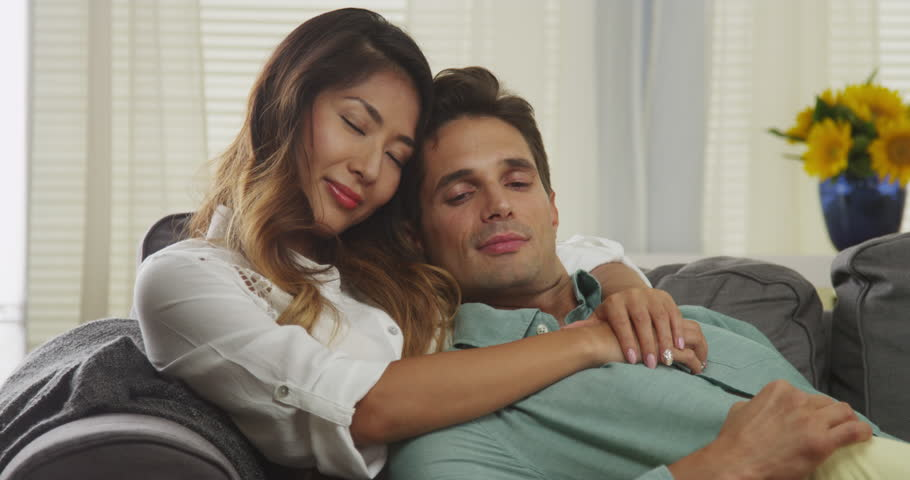Interracial couple cuddling on couch