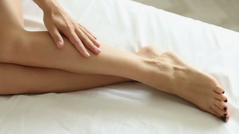 Woman with clean fresh skin smoothing her beautiful legs, slow motion