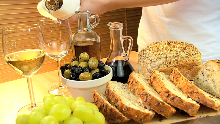 Selection of cheeses, whole-grain bread, oils & fruit with white wine for a healthy modern lifestyle lunch