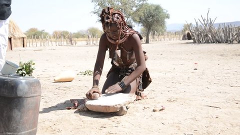 Namibia 08/24/2014: An Himba girl preparing the flour with stones. Himba, one of the oldest namibian tribes, live in his tradition not conforming to the new world rules and comfort..