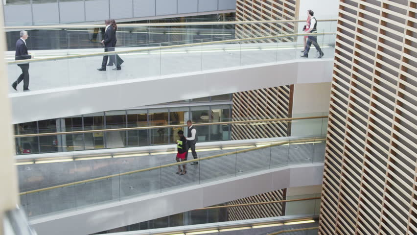 Businessmen meet & shake hands between floors of large modern office building | Shutterstock HD Video #7265206