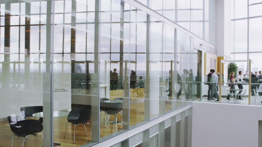 Business people in large office cafe area with views of the city skyline