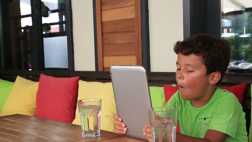 Child using digital tablet at the restaurant | Shutterstock HD Video #7287346