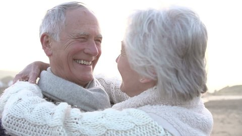 Romantic Senior Couple Embracing On Winter Beach In Slow Motion