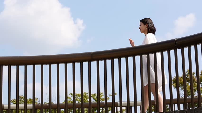 Young Japanese woman walking on elevated walkway in a park | Shutterstock HD Video #7404436