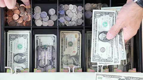 Man dispensing change from a register cash drawer.