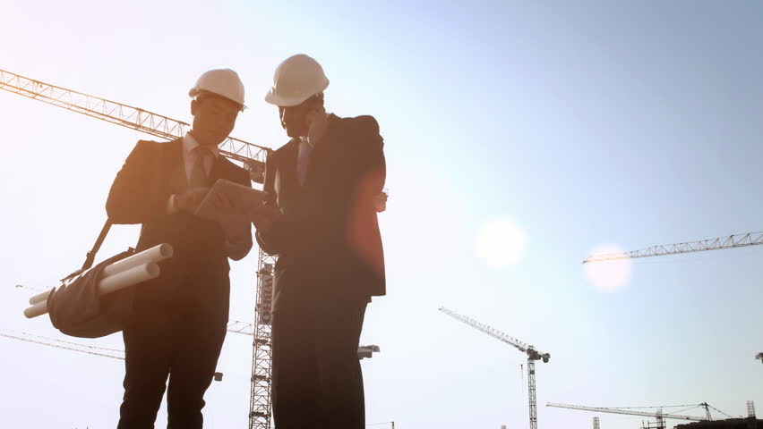 Steadicam shot of skyline and cranes, Asian construction/ executive/ architect/ engineer consultant discussing plans on tablet computer of new urban development with caucasian construction executive. | Shutterstock HD Video #7412995