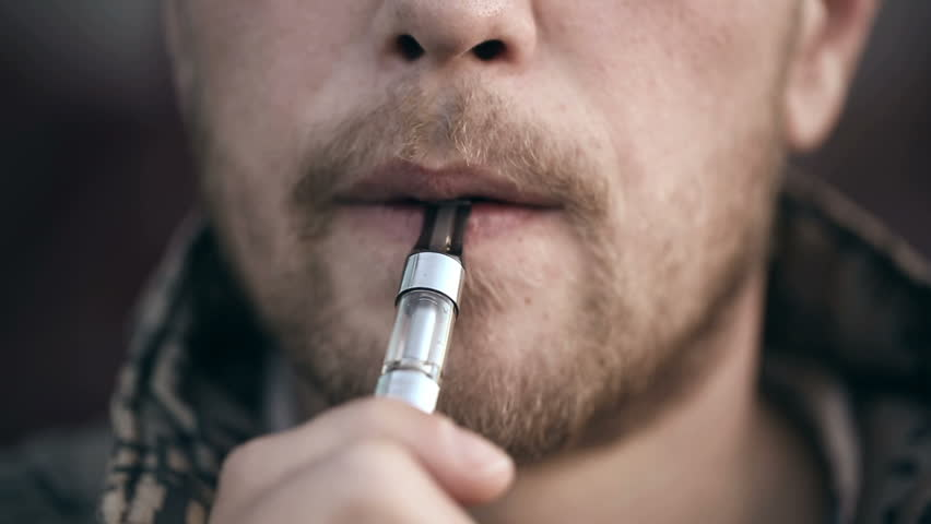 Close up of a bearded man smoking electronic cigarette.