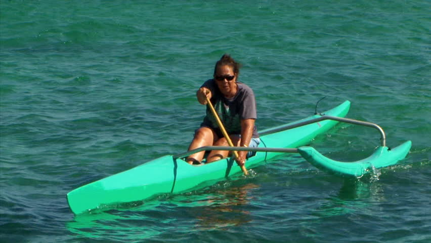 3fc5232682 A woman in an outrigger canoe paddles in the beautiful turquoise ocean