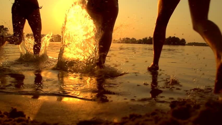 Group of happy girls running and playing in water at the beach on sunset. Beauty and joyful teenager friends having fun, dancing, spraying over summer sunset. Beach party. Sun flare. Slow motion 1080p | Shutterstock HD Video #7459492