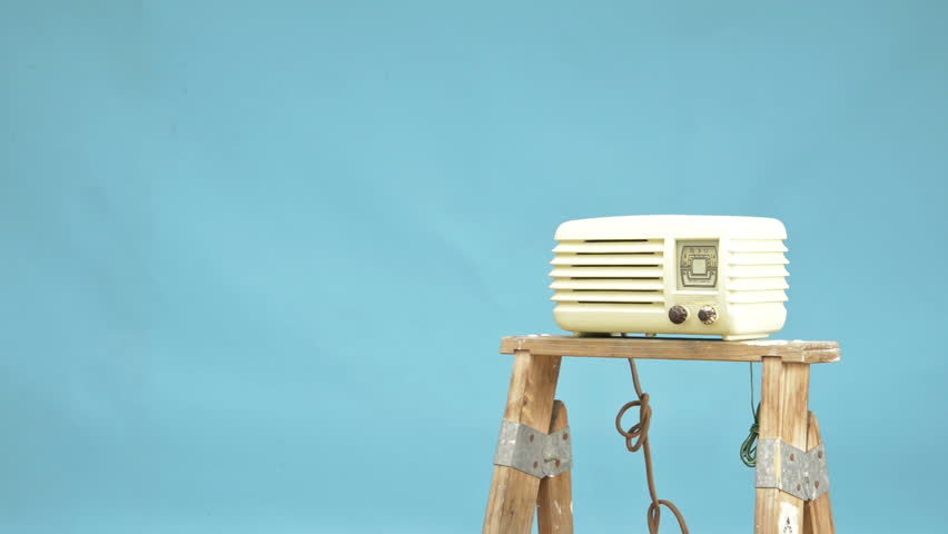 An untidy bizarre man, wearing big patched glasses and a toupee, trying to tune in a station on an antique tube bakelite radio, over light blue background