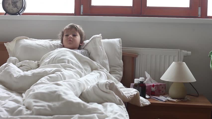 Sick boy, lying in bed, mother checking his temperature and giving him medicine
