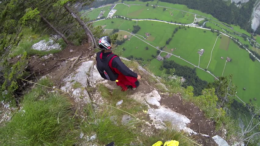 A base jumper in a wingsuit jumps from a cliff, gliding down over a green landscape, houses visible below, POV