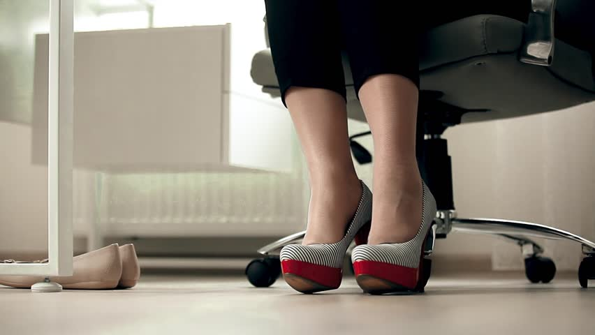 Closeup View Of Businesswoman Taking High Heeled Shoes Under Table At Office