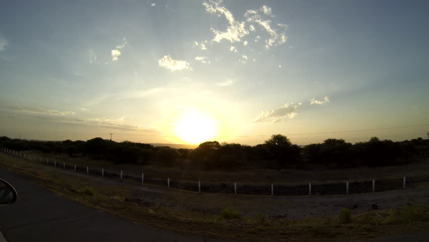 Sun setting over the horizon as seen from a moving vehicle | Shutterstock HD Video #7483450