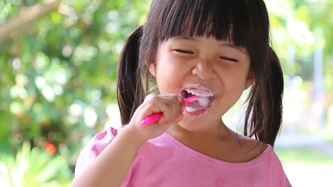 Cute Asian Little Girl Brushing Teeth