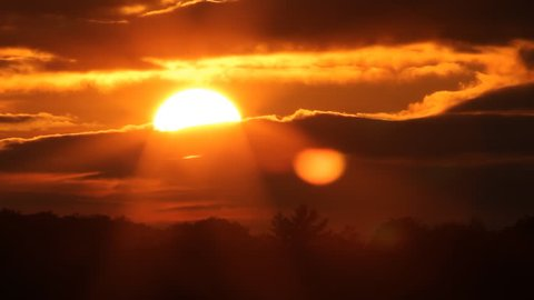 Fiery sunset with sun into clouds. Timelapse. Sunset in Muskoka, Ontario, Canada. Timelapse.