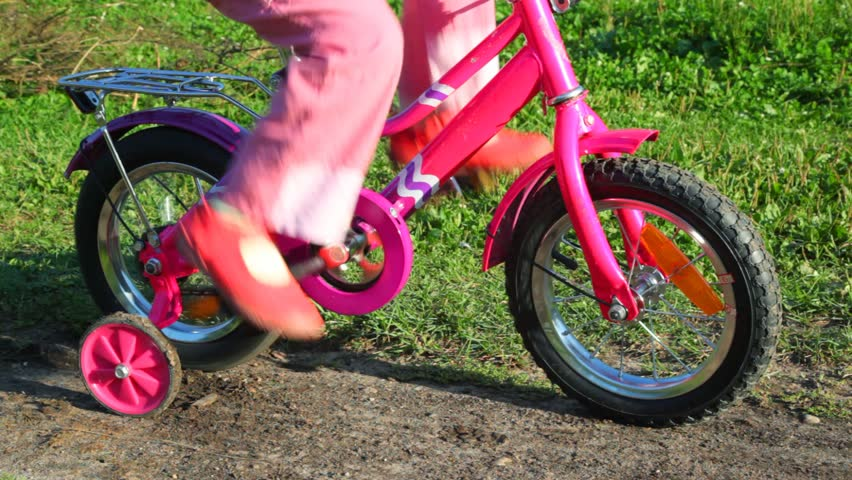 legs of little girl pedaling stopped bicycle in summer park