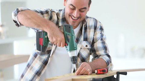 Man at home using electric drill