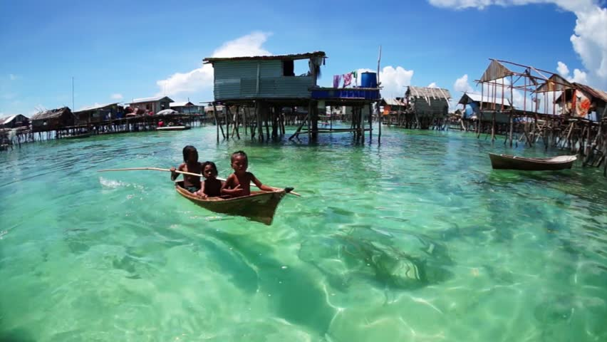 OMADAL ISLAND, SABAH, MALAYSIA - JUNE 6 : Unidentified Sea Bajau's children rowing a boat June 6th, 2014 in Omadal Island, Sabah Malaysia #7571926