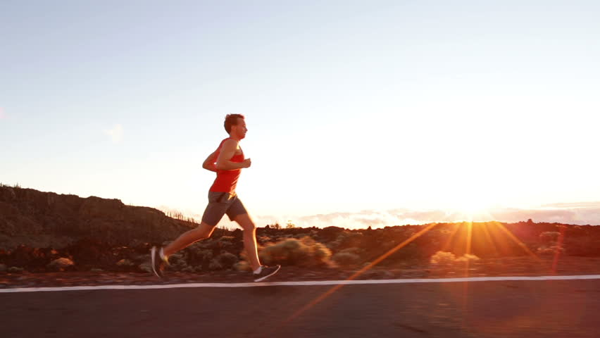 Runner - athlete man running training outdoors exercising on mountain road at sunset in amazing landscape nature. Fit handsome athletic male working out for marathon run outside in summer.   Shutterstock HD Video #7587916