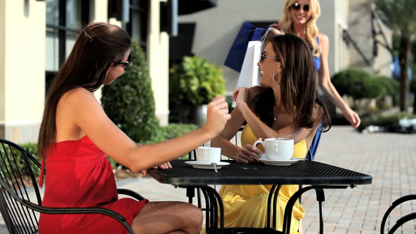 Three sophisticated female friends meeting at outdoor cafe after a successful shopping trip