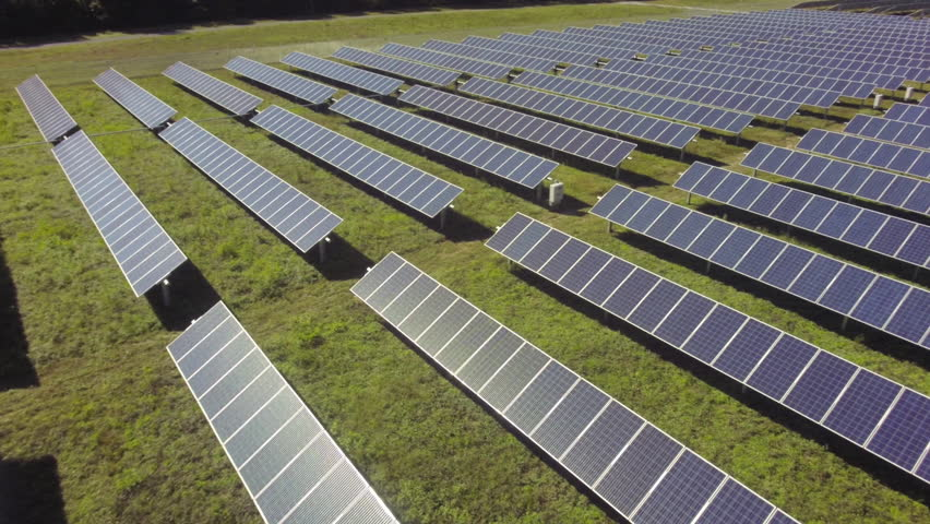 Aerial view flying over solar panels, sun shining back at camera stock video footage clip