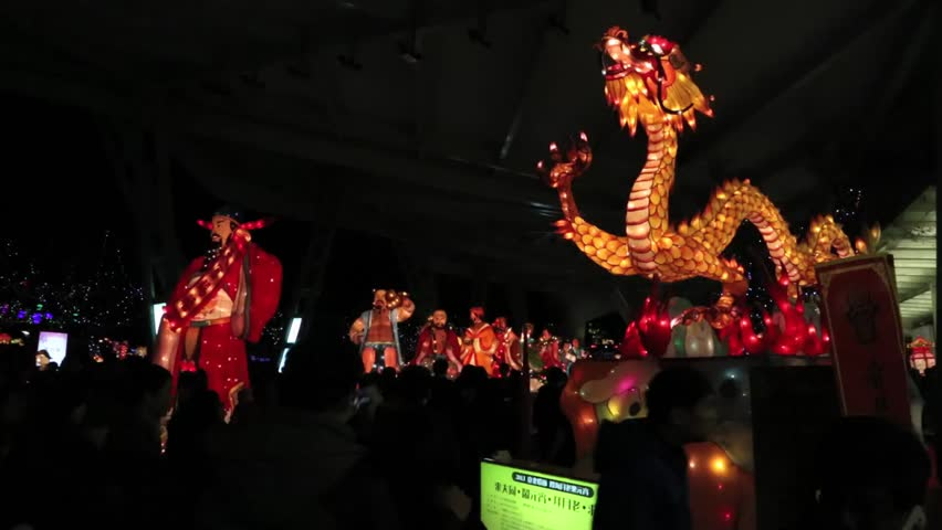Taipei, Taiwan-24 February, 2013: Gods and dragon Chineses lanterns in line in the Taipei Light Festival, silhouette people walking and take picture with the phone-Dan | Shutterstock HD Video #7648186