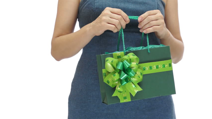 An anonymous woman in a blue dress holding a green gift bag torso of an anonymous woman in a blue dress holding a green gift bag decorated with negle Gallery