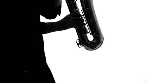Close up of dark silhouette of musician playing the saxophone
