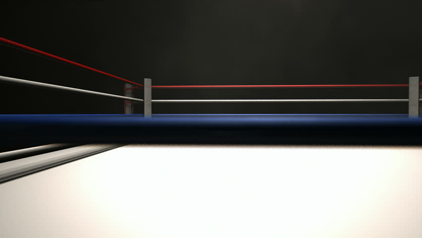 A pan across a empty regular boxing ring surrounded by ropes spotlit in the middle on an isolated dark background