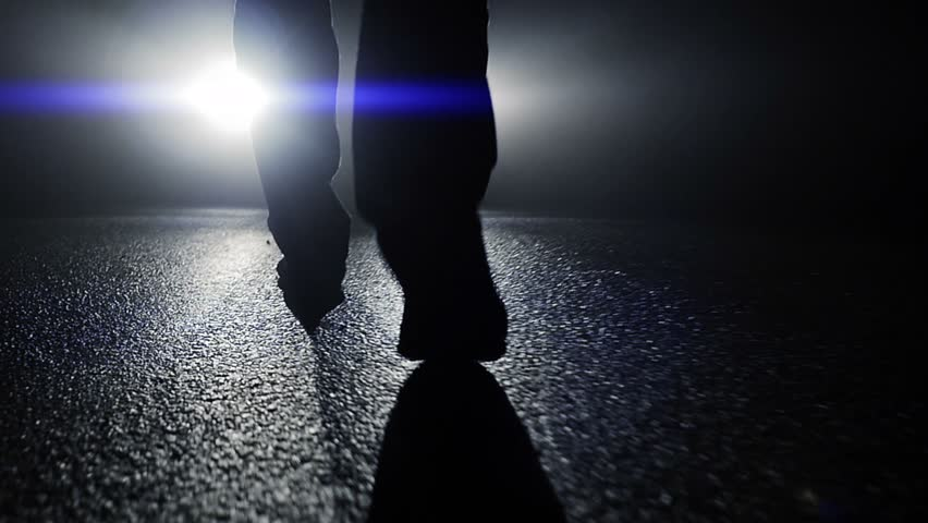 camera following feet walking towards car light beams in dark night. foot steps close up