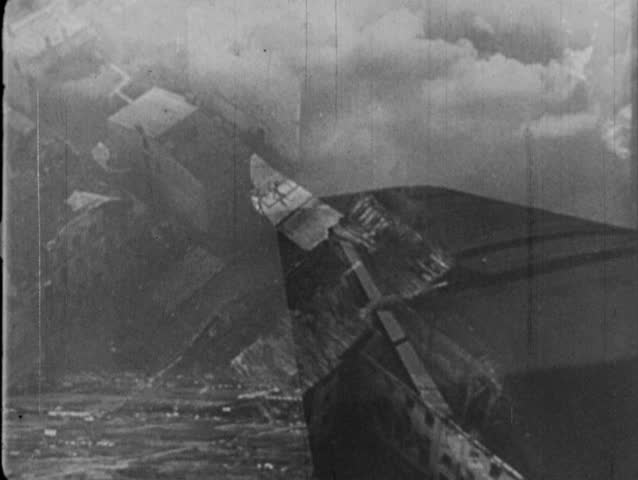 EUROPE- CIRCA 1939-1944: POV from aerial bomber over urban landscape, smoke billows from destroyed buildings.