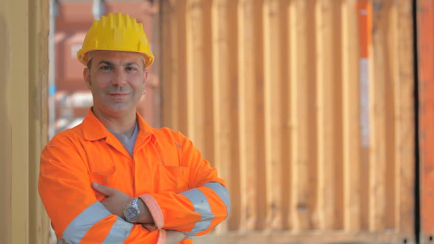 Portrait of mid adult worker leaning on cargo container and looking at camera. Horizontal shape, front view, copy space
