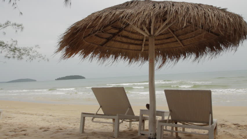 Two White Sun Loungers Site Under A Palm Leaf Parasol Umbrella While The Waves Roll Into