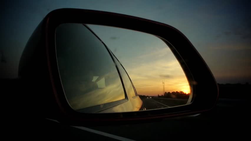 Car driving with vivid sunset (sun going down) in read side mirror. Other cars are reflected as well as the trees and bridges