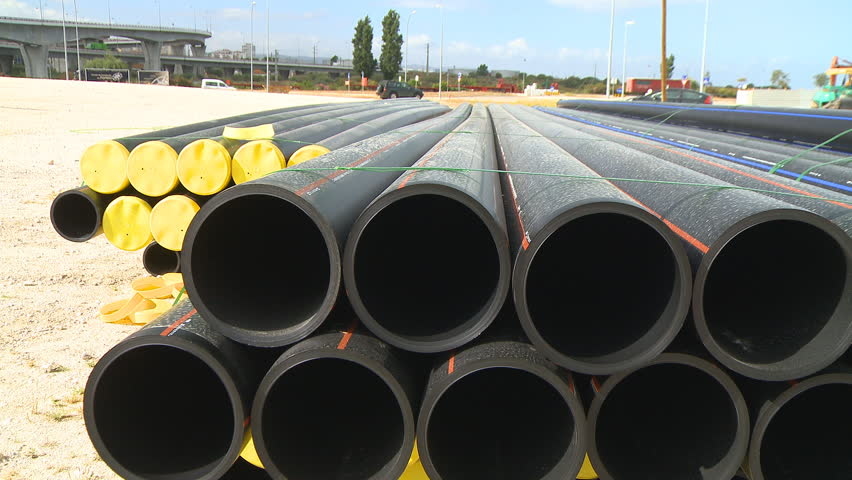 Pipes stacked in construction site dolly shot