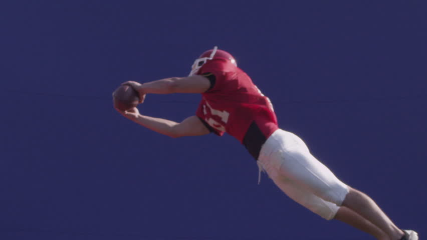 A football player catches a football with bluescreen. HD 720p. Shot on Red One.