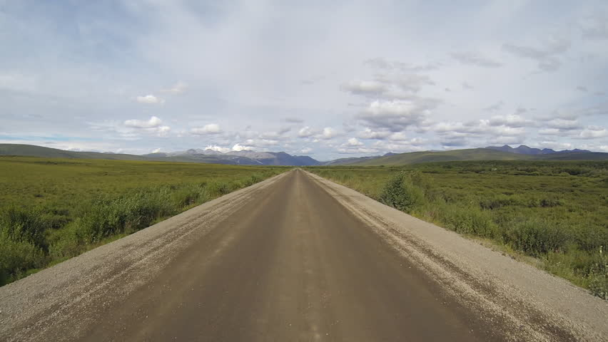 Long lonely open road through tundra heading north on the Dempster Highway toward Inuvik, Yukon Territory, Canada, in summer.  Driving POV.