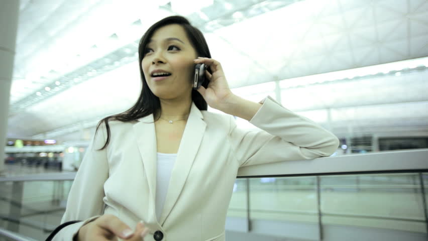 American Asian Chinese woman airport passenger travel business wireless smart phone information departures luggage executive traveller | Shutterstock HD Video #7853875