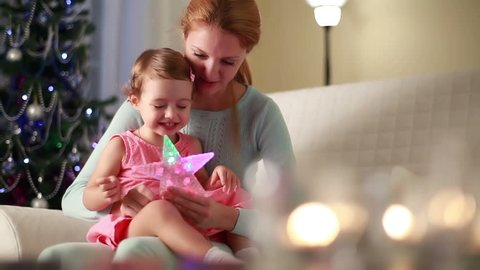 Young charming mother and her cute daughter playing with Christmas stars.
