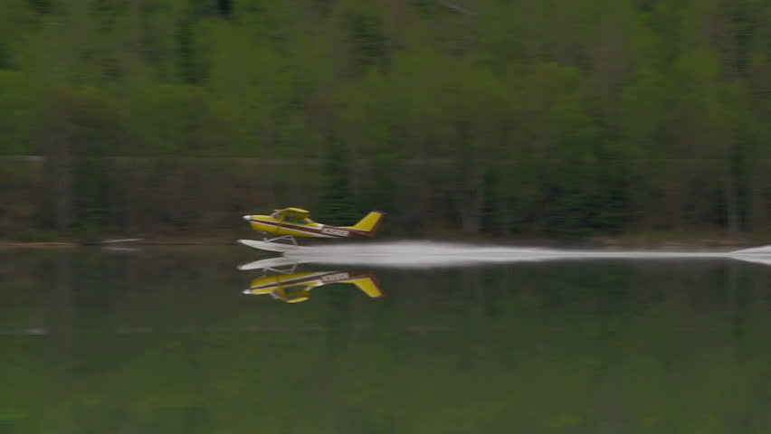 Moose Lake, AK - July 2012: Yellow floatplane taking off from mountain lake in Alaska.
