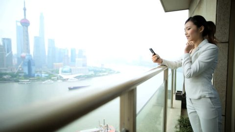 Asian Chinese American female financial advisor business meeting China Shanghai downtown city luxury apartment wireless cloud smart phone