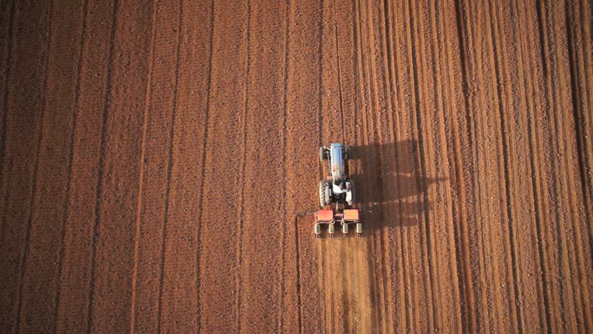 Aerial of tractor on harvest field (top view from height)
