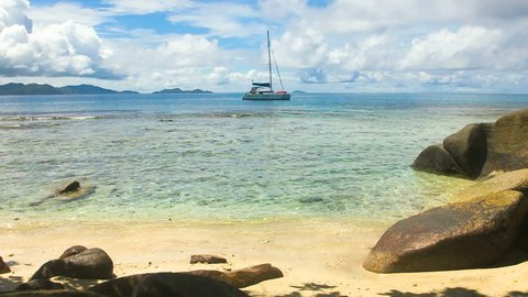 View from the bay onto a sailing boat floating in the ocean. In the front various sized boulders and the beach are visible. The ocean water is crystal clear and the clouds in the sky are picturesque.