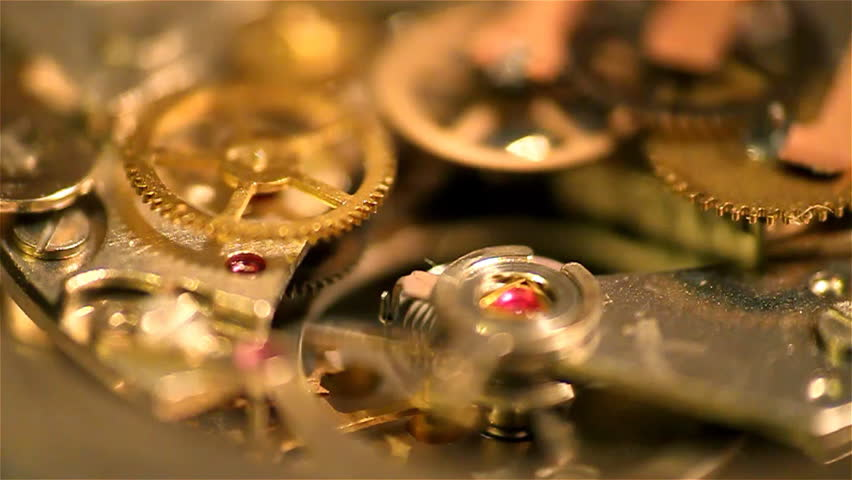 A low angled macro shot of cogs spinning inside a watch.
