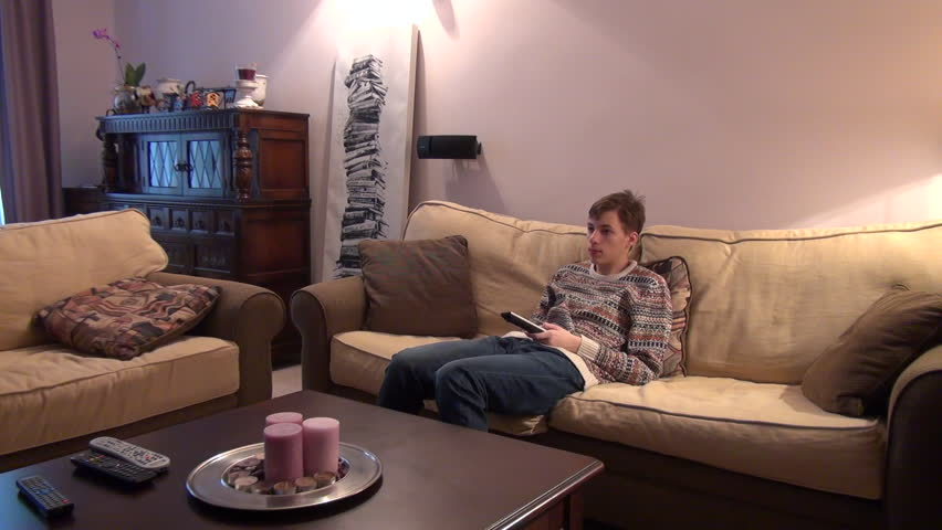 Leisure time, bored teenage boy watching TV, lying on a couch, changes channels | Shutterstock HD Video #7918246